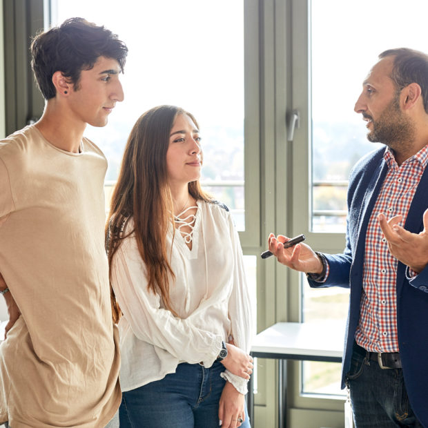 Students talk to a professor about their Bachelor thesis
