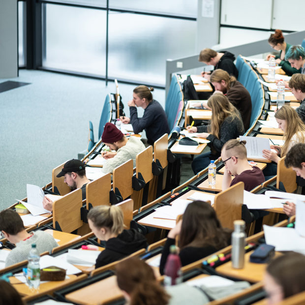 Students sit in the lecture hall and actively participate in the lecture